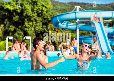 Young couple in swimming pool on sunny day. Water slide. - Stock Photo