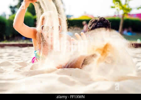 Couple lying on the sandy beach on sunny summer day - Stock Photo
