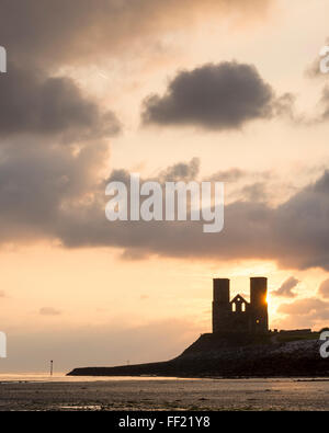 The Sun rising behind the twin towers of St. Mary's Church at Reculver on the North Kent coast. - Stock Photo