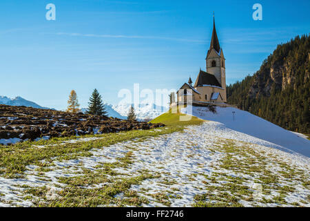 The church of the little village of Schmitten surrounded by snow, Albula District, Canton of Graubunden, Switzerland, - Stock Photo