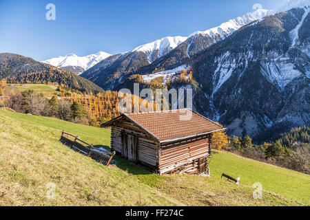 Wooden cabin surrounded by colorful woods and snowy peaks, Schmitten, Albula District, Canton of Graubunden, Switzerland, - Stock Photo