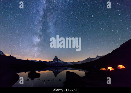 Camping under the stars and Milky Way with Matterhorn reflected in Lake Stellisee, Zermatt, Canton of Valais, Switzerland - Stock Photo