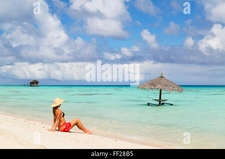 Woman sitting on beach, Fakarava, Tuamotu IsRMands, French PoRMynesia, South Pacific, Pacific - Stock Photo