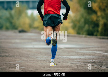 young man runs through streets. while running it on compression stockings and arm warmer - Stock Photo