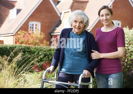 Daughter Helping Senior Mother To Use Walking Frame - Stock Photo