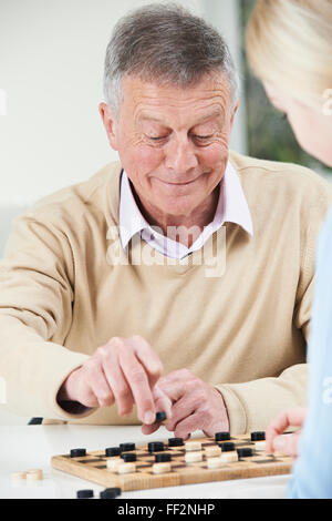Senior Man Playing Checkers With Teenage Daughter - Stock Photo