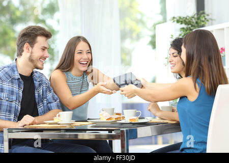 Friends celebrating birthday and giving gift to a girl sitting in a dining room - Stock Photo