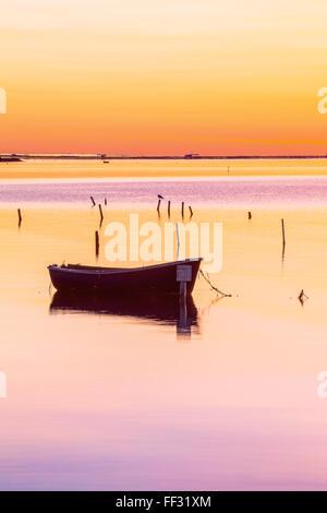 Sunrise on the Ebro delta with boat near shellfish farming - Stock Photo