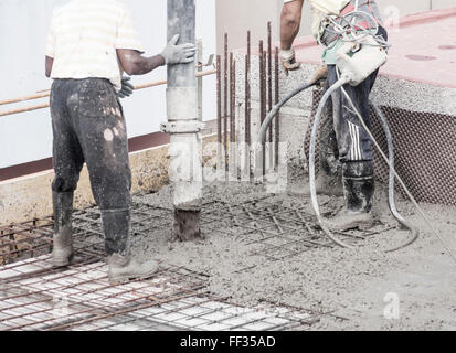 Pouring cement on construction site and removing air bubbles from newly poured concrete with vibrating poker - Stock Photo