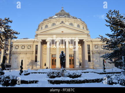 A statue of poet Mihai Eminescu stands in the snow outside the Romanian Athenaeum, the city's main concert hall. - Stock Photo