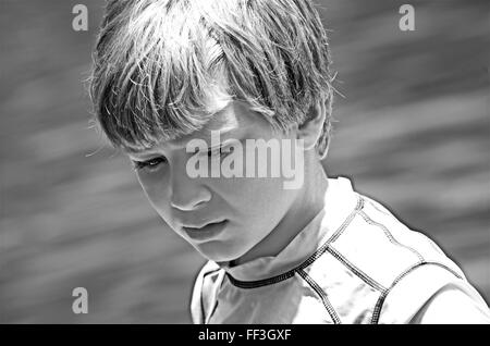 A young boy with thoughtful expression in black and white. - Stock Photo