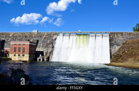 Water flowing through the gates of a dam after a storm. - Stock Photo