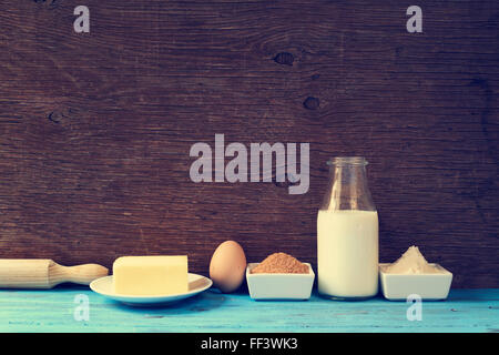some ingredients for preparing cookies or a cake, such as milk, eggs, flour, butter and brown sugar on a blue rustic - Stock Photo