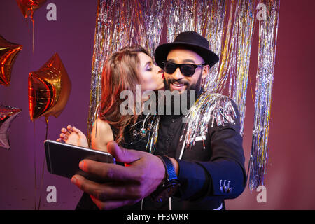 Multiethni? young couple kissing and taking selfie over purple background - Stock Photo