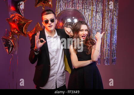 Beautiful young couple having party and showing thumbs up and ok gesture over purple background