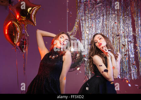 Two charming playful young women in black dresses dancing and having party over purple background - Stock Photo