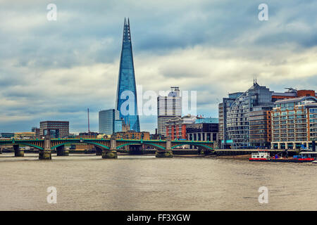 View of modern buildings along Thames river and Shard on background under cloudy sky in London, UK (toned). - Stock Photo