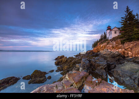 The iconic Bass Harbor Head Lighthouse is reflected in a tidepool at sunrise in Acadia National Park, Mount Desert - Stock Photo
