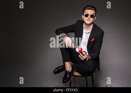 Young man in trendy cloth sitting on the chair and holding box with a proposal ring over black background - Stock Photo