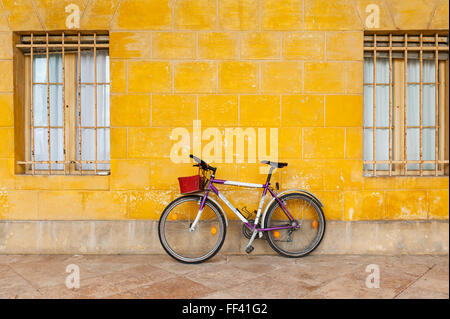 Northern Italy. A purple bicycle with a bright red wicker basket leaning against a stucco wall painted with yellow - Stock Photo