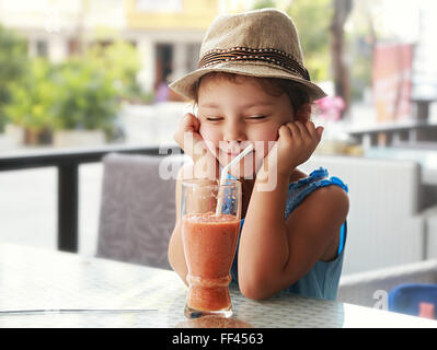 Fun kid girl in hat screwing up her eyes and waiting the moment to drink the smoothie tasty juice on summer background - Stock Photo