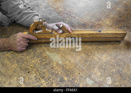 Carpenters hands hold planer tool on a vintage wooden background - Stock Photo