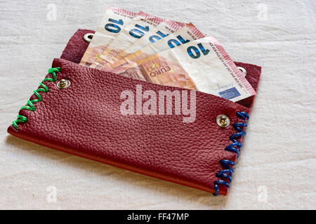 Ten Euro notes in an open purse with colorful stitches on either side lying on a table in a financial concept - Stock Photo