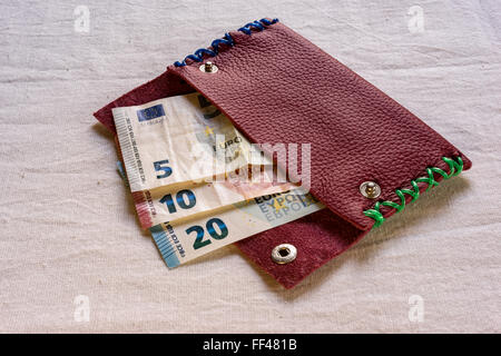 Euro banknotes in different denominations, a 5, 10, and 20 Euro note, protruding from an open purse on a table, - Stock Photo