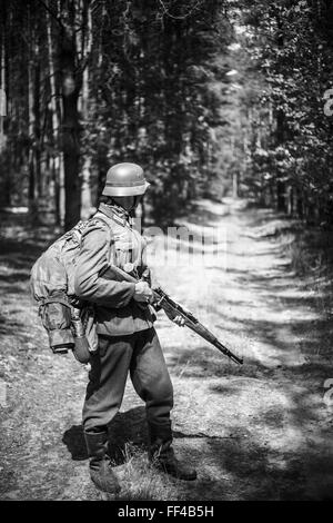 Unidentified re-enactor dressed as German soldier with rifle standing on road in woods. Black and white colors - Stock Photo