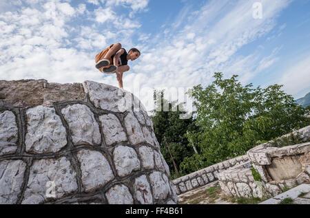Young boy praticing parkour in Vraca Memorial Park, Sarajevo, Bosnia and Herzegovina - Stock Photo