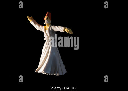 Whirling dervish isolated on black background - Stock Photo