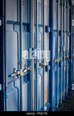 A row of Blue Self Storage Shipping Containers in a secure compound - Stock Photo