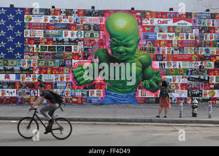 A man cycles to work past a Ron English art collage on the Bowery Mural Wall on Houston Street in New York - Stock Photo