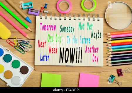 Tomorrow Someday Not Yet NOW written on notebook - Stock Photo