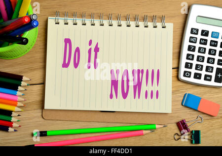 Do it now written on notebook - Stock Photo