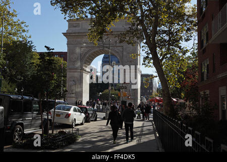 People walk south down Fifth Avenue into Washington Square Park on a warm autumn day - Stock Photo