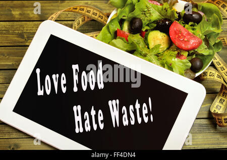 Love food Hate waste written on digital tablet - Stock Photo