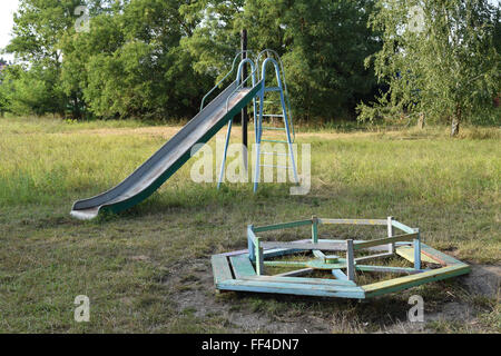Children playground. Swings and a slide to slide. - Stock Photo
