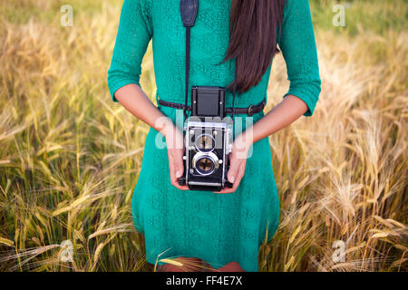 Vintage photo, brunette girl with retro camera in meadow - Stock Photo