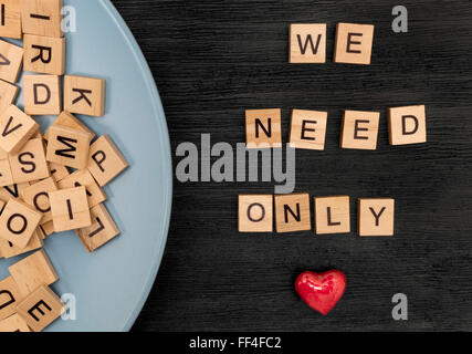 Wooden letters spelling we need only love - Stock Photo