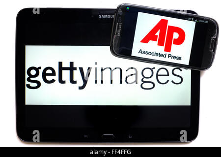 The AP logo on a smartphone and Getty Images on a tablet photographed against a white background. - Stock Photo