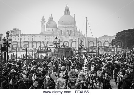 VENICE, ITALY - 09 FEBRUARY 2016: Monochrome image showing crowds and carnival revelers gathering in Venice to enjoy - Stock Photo