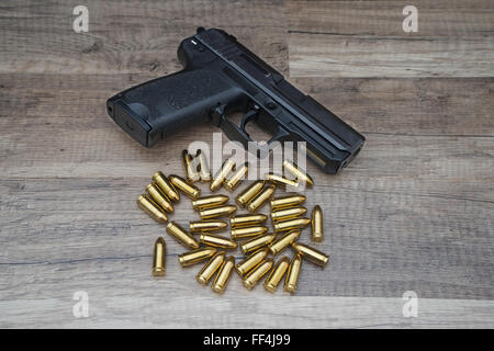 Gun pistol with bullets on wooden background. - Stock Photo