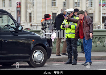 London, UK, 10 February 2016, Taxi driver protests as policeman writes ticket. Police stop taxi on Westminster bridge - Stock Photo