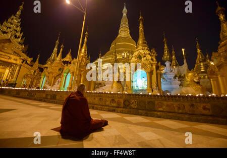 Monk praying at Shwedagon Paya, the holiest pilgrimage site in Yangon, Myanmar - Stock Photo