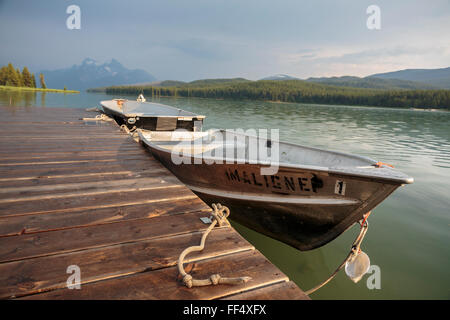 Evening light over Jasper National Park's Maligne Lake and boats available for rent at the historic Curly Phillips - Stock Photo