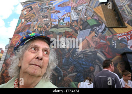 Mrs Betty Papworth a veteran peace campaigner stands in front of the Cable Street mural on the 70th anniversary - Stock Photo