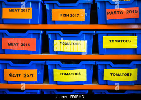 Organized food storage in plastic boxes on shelves in the Trussell Trust foodbank distribution centre in Wadebridge, - Stock Photo