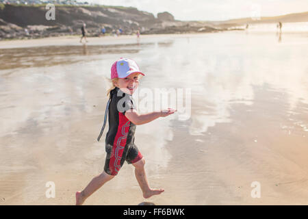 A child in a wetsuit running on sand - Stock Photo