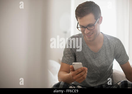 A working day. A man in pyjamas checking his smart phone. - Stock Photo